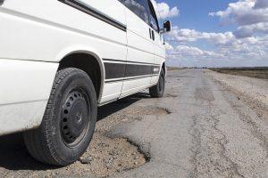 Dangers of potholes - car tyres driving through potholes
